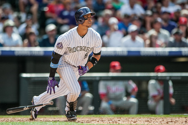 DENVER, CO - JUNE 16: Carlos Gonzalez #5 of the Colorado Rockies watches the flight of a two-run eighth inning home run against the Philadelphia Phillies at Coors Field on June 16, 2013 in Denver, Colorado. The Rockies beat the Phillies 5-2.